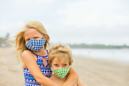 Children in stylish masks have fun on sea sand beach. New rules to wear face covering at public places. Cancelled cruise, tour due coronavirus COVID 19. Family summer vacation, travel lifestyle. Foto de archivo