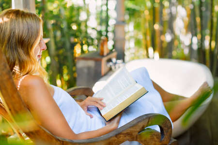 Attractive girl sit at rocking chair drinking morning coffee, reading romance in paper book. Relaxing woman fill bath tub in Boho style outside bathroom in luxury villa on summer tropical vacation. Standard-Bild