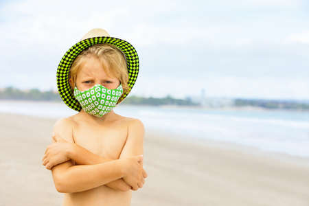 Child in straw hat, stylish masks have fun on sea beach. New rules to wear face covering at public places. Cancelled cruise, tour due to virus . Family summer vacation, travel lifestyle.