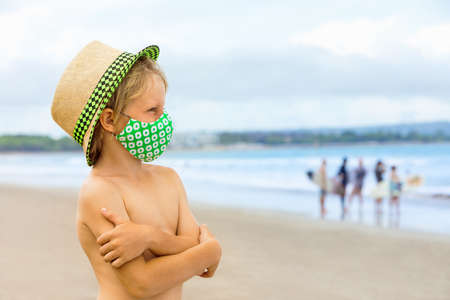 Child in straw hat, stylish masks have fun on sea beach. New rules to wear face covering at public places. Cancelled cruise, tour due virus  Family summer vacation, travel lifestyle. Foto de archivo