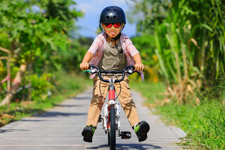 Young rider kid in helmet and sunglasses riding bicycle.