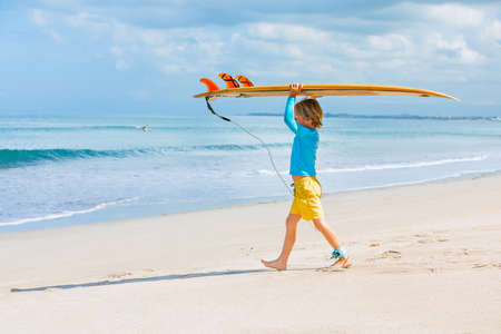 Happy surf boy - young surfer learn to ride on surfboard with fun on sea waves. Foto de archivo