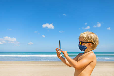 Funny boy taking selfie photo by smartphone on tropical sea beach. New rules to wear cloth face covering mask at public places