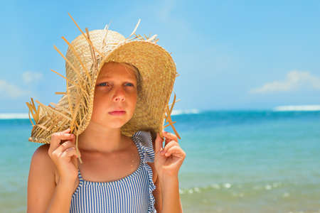 Young positive girl in straw hat at tropical beach.