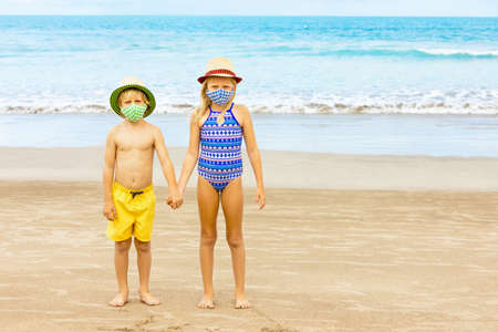 Kids in straw hat, stylish masks have fun on sea beach. New rules to wear face covering at public places.