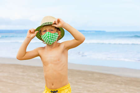 Child in straw hat, stylish masks have fun on sea beach. New rules to wear face covering at public places. Foto de archivo