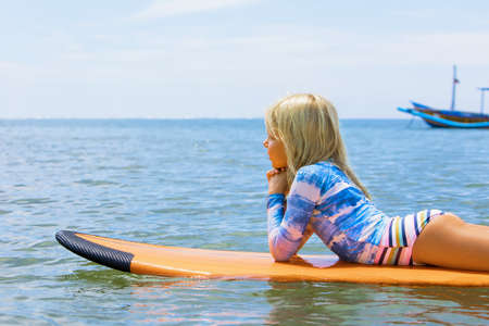 Happy girl relaxing before surfing. Surfer lying on surf board, look at sky. People in water sport adventure camp, extreme activity on family summer beach vacation. Watersport background