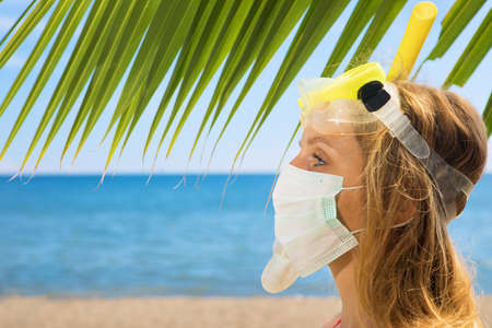 Funny girl in medical and snorkeling masks on sea beach.