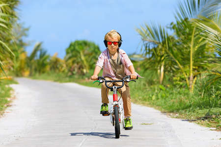 Young rider kid in headphones and sunglasses riding bicycle.