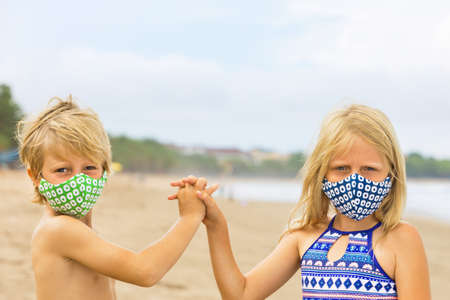 Children in stylish masks have fun on sea sand beach. New rules to wear face covering at public places.