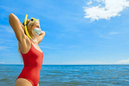 Funny girl in medical and snorkeling masks on sea beach. New rules to wear face covering at public places.