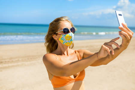 Funny girl taking selfie photo by smartphone on tropical sea beach. New rules to wear cloth face covering mask at public places