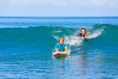 Little surf boy - young surfer learn to ride on surfboard with instructor at surfing school. Foto de archivo