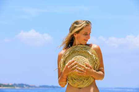 Young positive girl in straw hat have fun at tropical beach. Travel family lifestyle, recreational activities at summer cruise vacations. Foto de archivo