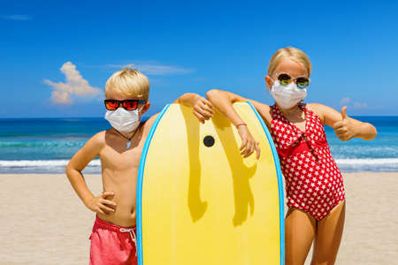 Young surfer kids with body board wearing sunglasses, protective masks on sea beach.