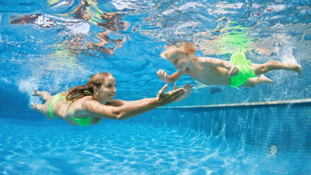 Happy people dive underwater with fun. Funny photo of mother, child in aqua park swimming pool. Family lifestyle, kids water sports activity, swimming lesson with parents on summer holiday Foto de archivo
