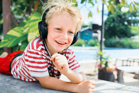 Young positive child in headphones listening music with fun at tropical beach party. Travel family lifestyle, recreational activities at summer cruise vacations.