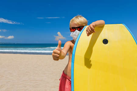 Young surfer boy with body board wearing sunglasses, protective masks on sea beach.