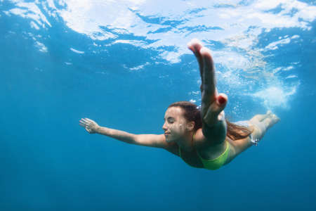 active teenage girl jump and dive underwater in tropical coral reef pool. Travel lifestyle, water sport, snorkeling adventure. Swimming lessons on summer sea beach vacation with kids