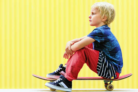 Little skater with skateboard have fun before children training class in skate park. Active family lifestyle, outdoor recreational activities on summer holidays in city. Kids sports and urban fashion.