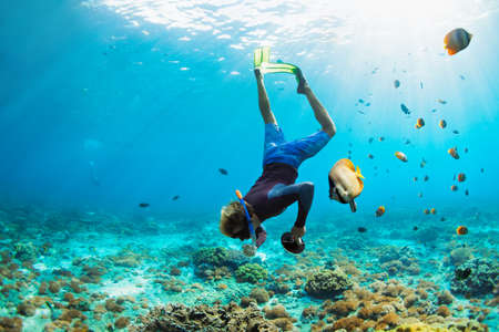 Happy family vacation. Man in snorkeling mask with camera dive underwater with tropical fishes in coral reef sea pool. Travel lifestyle, water sport outdoor adventure, swimming on summer beach holiday. Foto de archivo