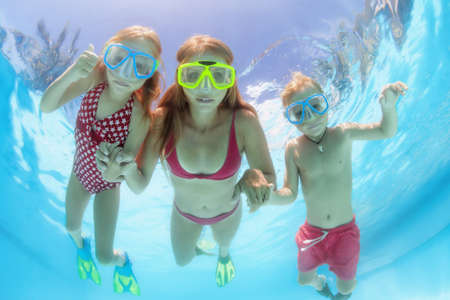 Happy people dive underwater with fun. Funny photo of mother, kids in snorkeling masks in aqua park swimming pool. Family lifestyle, children water sport activity, lesson with parent on summer holiday Foto de archivo