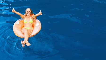 Photo of young woman swimming with fun on inflatable floating ring in sea water pool. Family travel lifestyle, kids with parents outdoor swimming activity on summer holidays at tropical beach resort Foto de archivo
