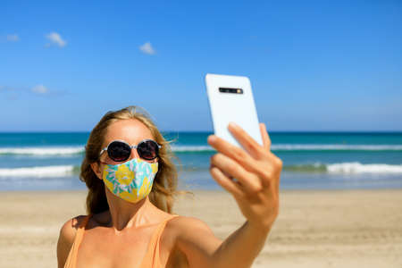 Funny girl taking selfie photo by smartphone on tropical sea beach. New rules to wear cloth face covering mask at public Foto de archivo