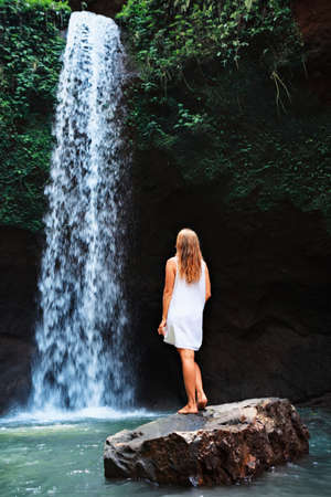 Young woman travel in Bali rainforest. Happy girl enjoy jungle nature. Stand in natural pool under waterfall, see on falling water. Walking day tour, hiking activity adventure on family summer holiday Foto de archivo