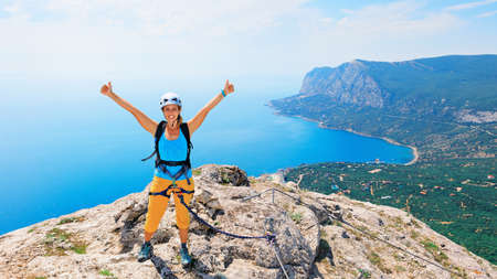 Happy young woman stand on mount top. Amazing sea landscape. Family travel adventure, hiking activity. Via ferrata tour with kids, exploring nature on summer vacation. Weekend day walking tour