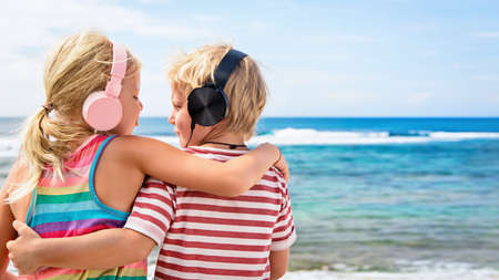 Young positive kids in headphones listening music with fun at tropical beach party. Travel family lifestyle, recreational activities at summer cruise vacations.