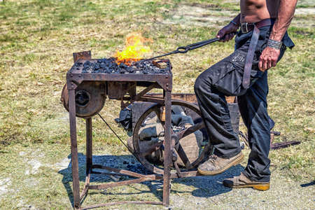 medieval blacksmith: Detail shot of metal being worked by craftsman at a blacksmith forge in medieval scenery.