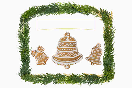 pine three: Homemade three bells in decoration gingerbread and honey cookies on nice christmas theme with a frame by pine tree twigs on white background with the free space for your own wishes.
