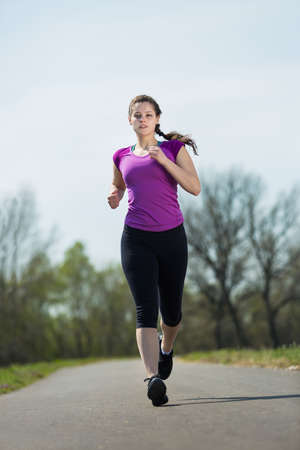 path to success: Young beautiful woman runner doing jogging path for success for a healthy lifestyle in natural landscape.