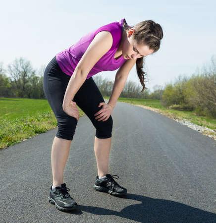 agotado: Mujer joven cansada que recuperar el aliento después del entrenamiento deportivo. Foto de archivo