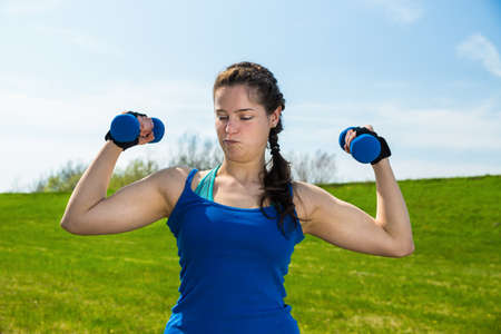 responsibly: Young woman in sportswear doing responsibly fitness exercise with two dumbbells . Stock Photo