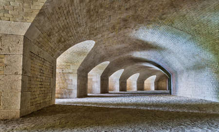 Castle tunnel interior with a series of arches in a ruined bastion fortress.
