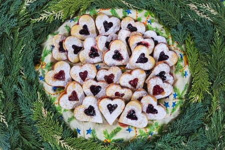 teacake: Jam shortbread cookies on pine tree twigs background .