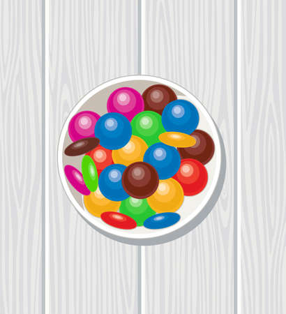 A bowl of rainbow colors and chocolate candy on gray wooden table