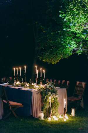 Wedding. Banquet. The chairs and table for guests, decorated with candles, served with cutlery and crockery and covered with a tablecloth. The table stands on a green lawn in the backyard banquet area Standard-Bild