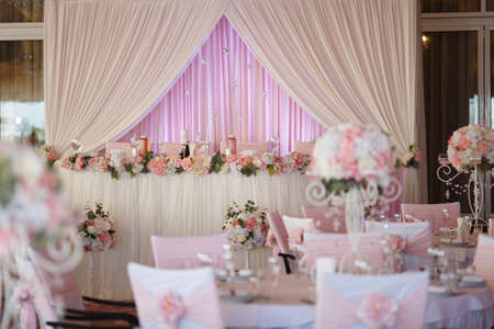 Wedding. Banquet. The chairs and table for guests, decorated with candles, served with cutlery and crockery and covered with a tablecloth. The table stands on a green lawn in the backyard banquet area Stock Photo