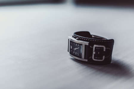 Minimalist wristwatch black dial on white background