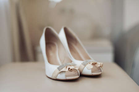Bride wedding shoes with high heels and silver brilliant earrings on sheeps clothing Stock Photo