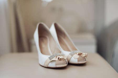 Mariée chaussures de mariage avec des talons hauts et des boucles d'oreilles brillantes en argent sur les vêtements de brebis Banque d'images - 82620507