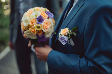 Wedding groom with brides bouquet of flowers outside