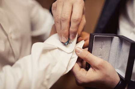cuff link: The groom fastens the cufflink on the shirt sleeve close-up