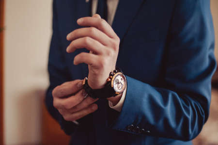 cuff link: The man fastens the watch on his hand Stock Photo