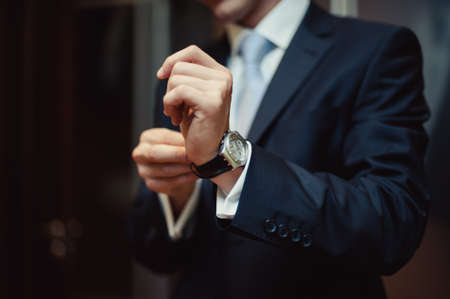 The man fastens the watch on his hand Stockfoto