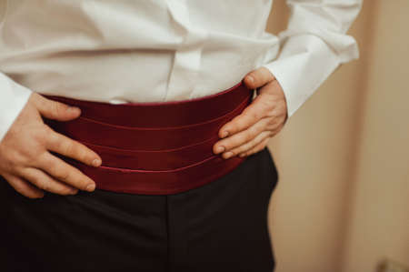cuff link: Groom holding hands on the belt, wedding suit Stock Photo