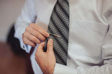 The groom puts on his tie a business man is dressing a tie stock the groom puts on his tie a business man is dressing a tie photo ccuart Choice Image